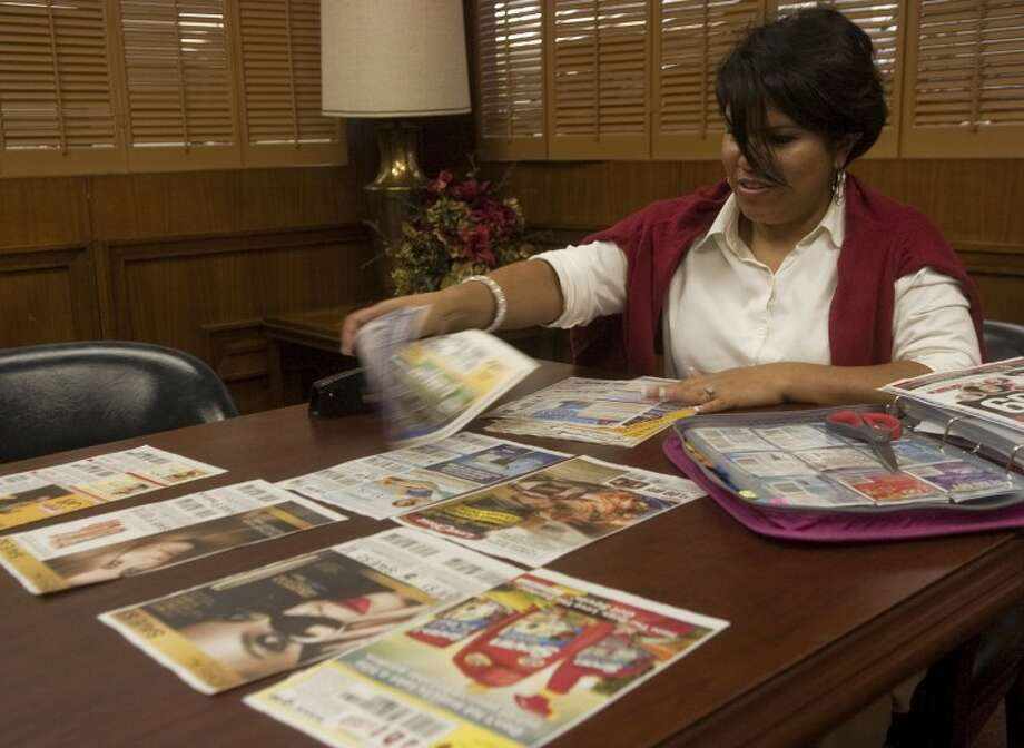 Celestine Lunda buys four Sunday papers to get the extra coupons in the inserts and then rips each page of coupon out to place in a pile together. Photo by Tim Fischer/Midland Reporter-Telegram Photo: Tim Fischer