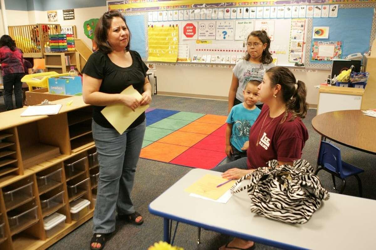 Pre-Kindergarten teacher Loretta Rodriguez meets with Susana Aranda, her son Jesus, 3, and daughter Margarita, 9, Thursday during Meet the Teacher night at Henderson Elementary. Cindeka Nealy/Reporter-Telegram