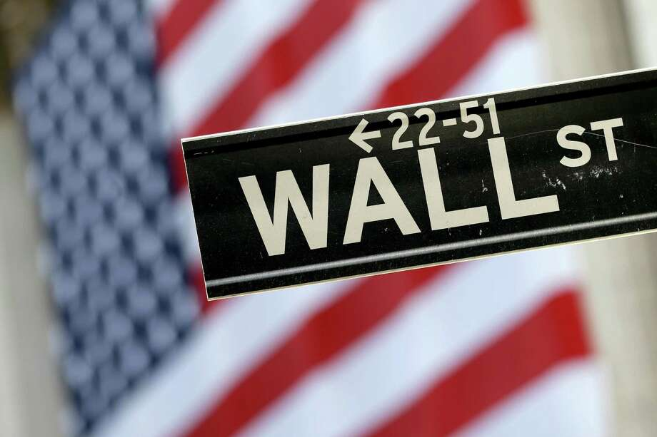 A Wall Street street sign is framed by a giant American flag hanging on the facade of the New York Stock Exchange, Tuesday, Sept. 8, 2015. U.S. stocks are opening solidly higher as traders come back from the Labor Day holiday. (AP Photo/Mary Altaffer) Photo: Mary Altaffer, STF / Copyright 2016 The Associated Press. All rights reserved. This material may not be published, broadcast, rewritten or redistribu