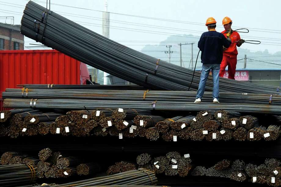 Workers load steel bars last month in Yichang, in central China's Hubei province. China's Cabinet has approved measures to boost exports.  Photo: STR / Chinatopix