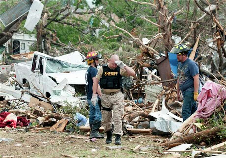 Emergency personnel look through debris on near Granbury, Texas on Thursday, May 16, 2013. Ten tornadoes touched down in several small communities in Texas overnight, leaving at least six people dead, dozens injured and hundreds homeless. Emergency responders were still searching for missing people Thursday afternoon. (AP Photo/Rex C. Curry) Photo: Rex C. Curry / FR41626AP