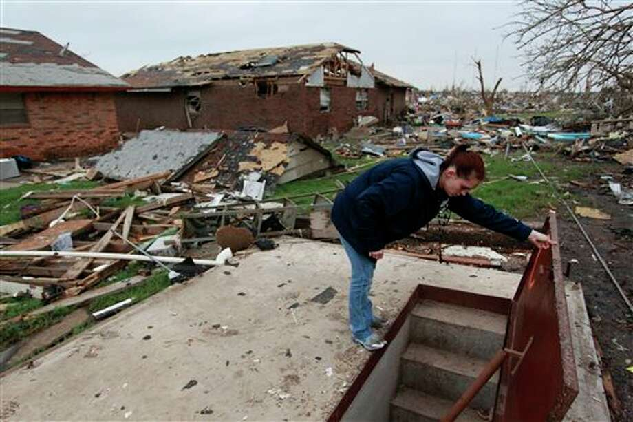 Sabrina Mitchell, 19, takes a peek inside the neighbor's storm shelter where she survived this week's deadly tornado, and emerged to find her home destroyed along with hundreds of others, in Moore, Okla., Friday, May 24, 2013. As a child, Mitchell attended Plaza Towers Elementary a few blocks away, where 9 children were killed when the tornado hit. (AP Photo/Brennan Linsley) Photo: Brennan Linsley / AP