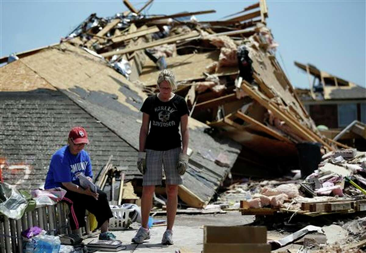 In this Wednesday, May 22, 2013 photo, in Moore, Okla,, Jennifer Walker, left, sifts through a memories book as she and her friend Kate Burger, center, stand in front of what remains of Walker's home. When she moved into her single-story brick house in Moore eight years ago, she considered installing a safe room or bunker to shield her family. She decided against it. This week as she stood in the rubble and watched two National Guardsmen dig through the wreckage of her home to retrieve her two-week-old washer and dryer, she made a vow: She'll build an underground bunker, even if she has to shell out $10,000.