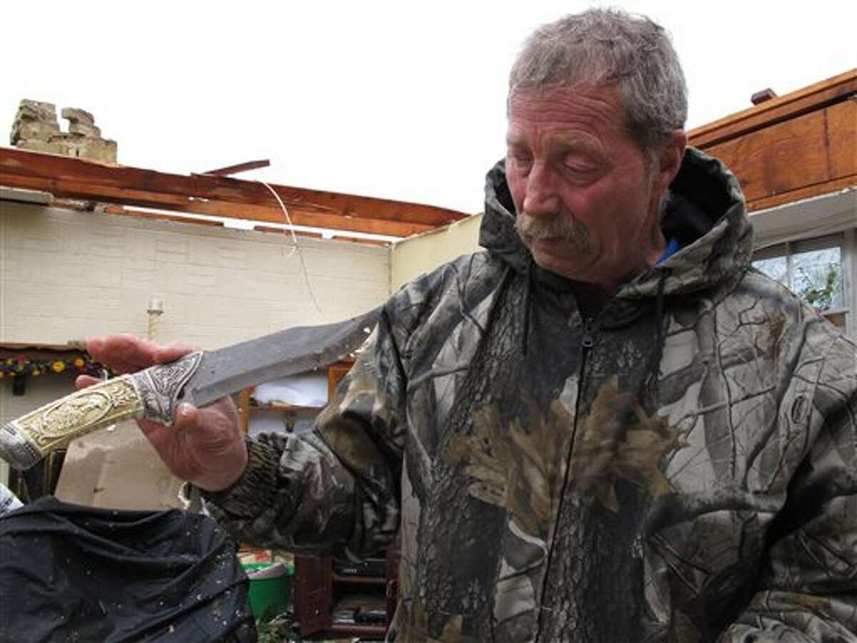 Wayne Osmus holds up an ivory-handled knife that he salvaged from the wrecked of his home in Moore, Okla., on Tuesday, May 21, 2013. Osmus' family was forced to hide in a closet Monday when winds prevented them from taking refuge in an underground shelter. (AP Photo/Allen Breed)