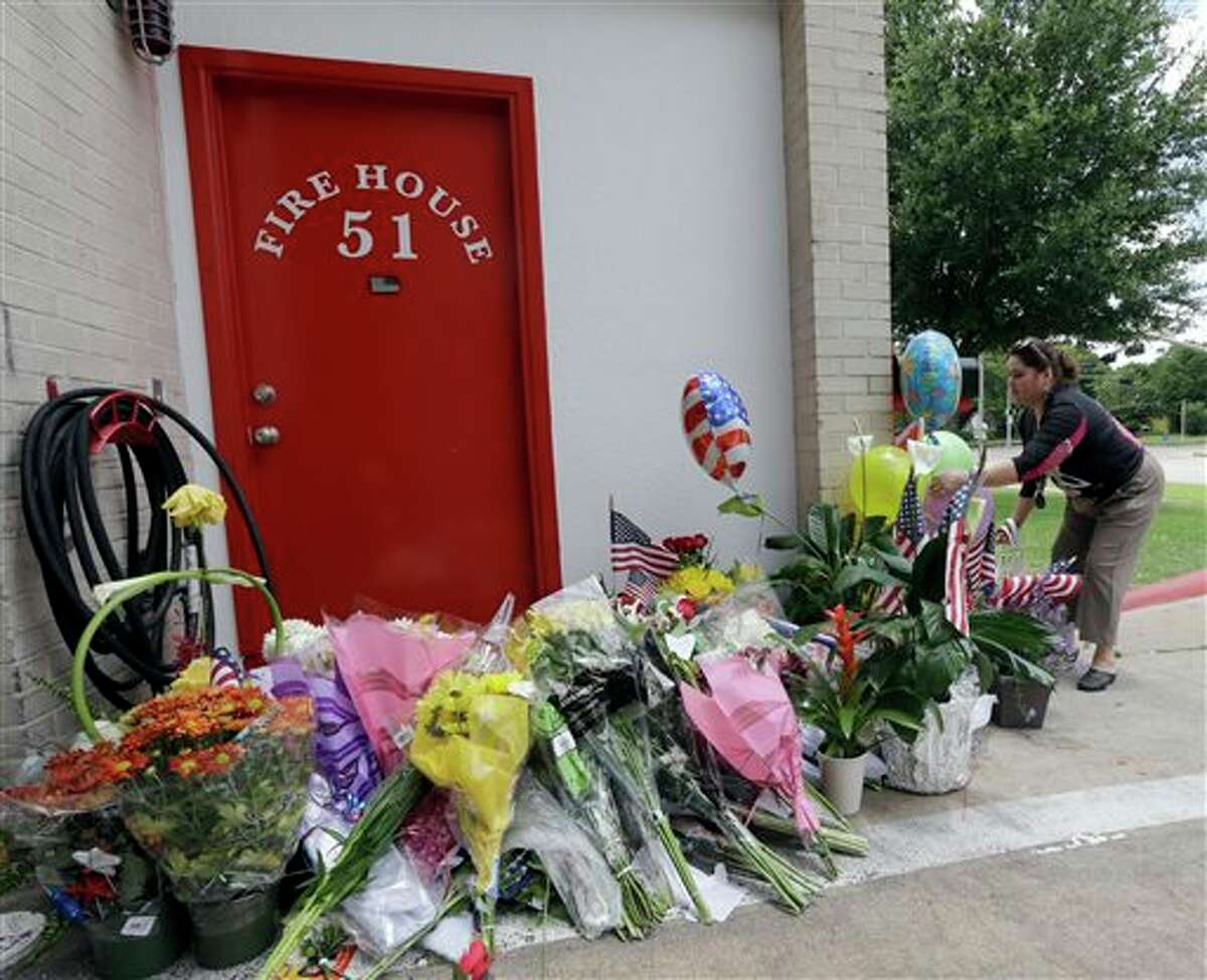 Rafala Santos places flowers at a makeshift memorial at Houston Fire Station 51, Saturday, June 1, 2013, in Houston. Four firefighters searching for people they thought might be trapped in a blazing Houston motel and restaurant Friday were killed when part of the structure collapsed and ensnared them, authorities said. (AP Photo/David J. Phillip)
