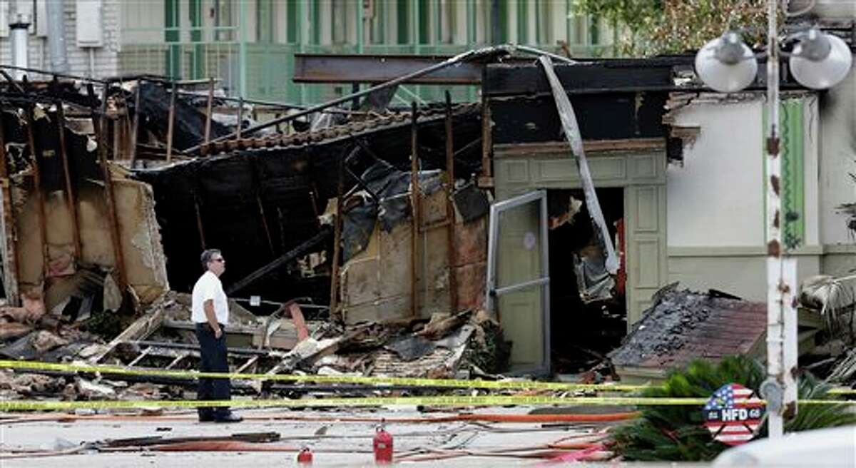 An official looks over the damaged scene the day after four firefighters died, Saturday, June 1, 2013, in Houston. Four firefighters searching for people they thought might be trapped in a blazing Houston motel and restaurant Friday were killed when part of the structure collapsed and ensnared them, authorities said. (AP Photo/David J. Phillip)