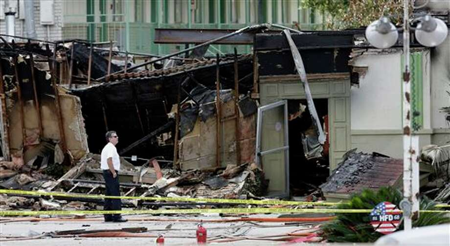 An official looks over the damaged scene the day after four firefighters died, Saturday, June 1, 2013, in Houston. Four firefighters searching for people they thought might be trapped in a blazing Houston motel and restaurant Friday were killed when part of the structure collapsed and ensnared them, authorities said. (AP Photo/David J. Phillip) Photo: David J. Phillip / AP