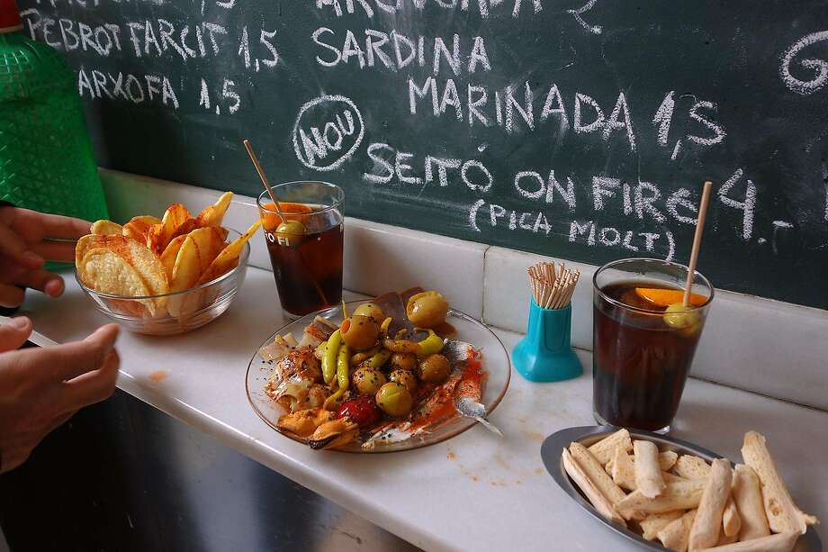 Standing at a bar with a sampler of tapas and chalkboard specials on the wall is a quintessential Spain experience. Photo: Rick Steves