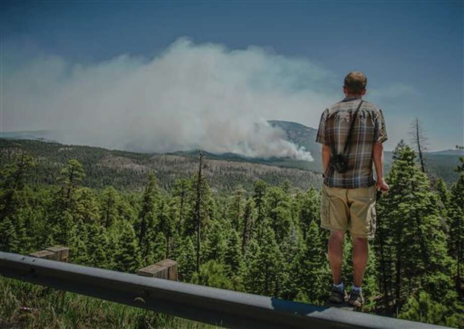 Jemez Springs resident Richard Middleton watches as the Thompson Ridge fire burns in an area just north of the town of Jemez Springs, New Mexico, Saturday, June 1, 2013. Fire crews in New Mexico on Saturday fought two growing wild blazes that have scorched thousands of acres, spurred evacuation calls for dozens of homes and poured smoke into the touristy state capital. (AP Photo/The Albuquerque Journal, Roberto E. Rosales) SANTA FE NEW MEXICAN OUT Photo: Roberto E. Rosales / Albuquerque Journal