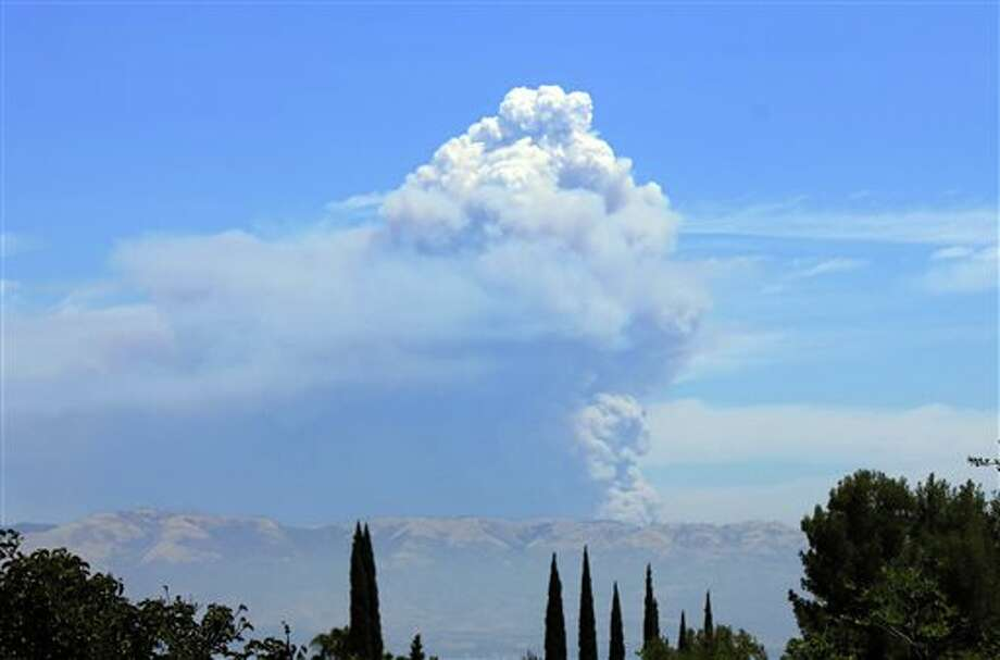 The Powerhouse Fire burning in the Angeles National Forest northwest of Los Angeles sends up a huge plume of smoke on Saturday, June 1, 2013. Smoke from the fire made visibility hazy in the San Fernando Valley, foreground. The blaze has burned thousands of acres of brush since it erupted Thursday afternoon near a utility powerhouse. (AP Photo/John Antczak) Photo: John  Antczak / AP