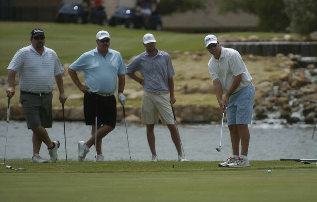 Teammates from left, Joe Frazier, Mark Terry and Matt Phillips watch the putt of Mike Connally during the final round of the Gusher four-man tournament at Green Tree Country Club. Len Hayward/Reporter-Telegram