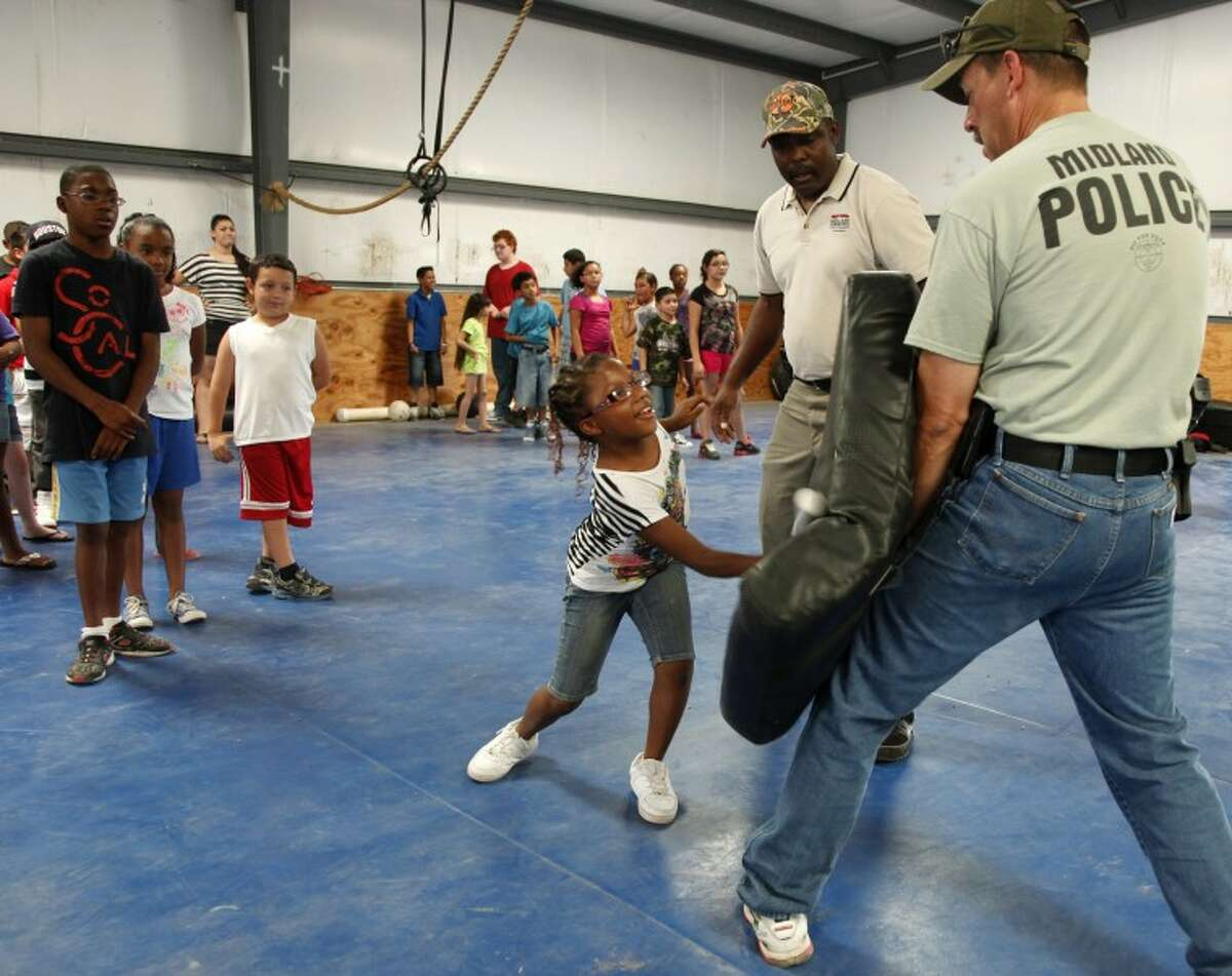 (2012 File Photo) Other kids of a camp with Casa de Amigos wait their turn while Marshayla Lewins, 9, uses a pratice baton to attack Officer Loren Frost Wednesday while getting a tour of the Permian Basin Police Acadamy and instuction on what police officers do on the job. Chaney Mitchell/Reporter-Telegram