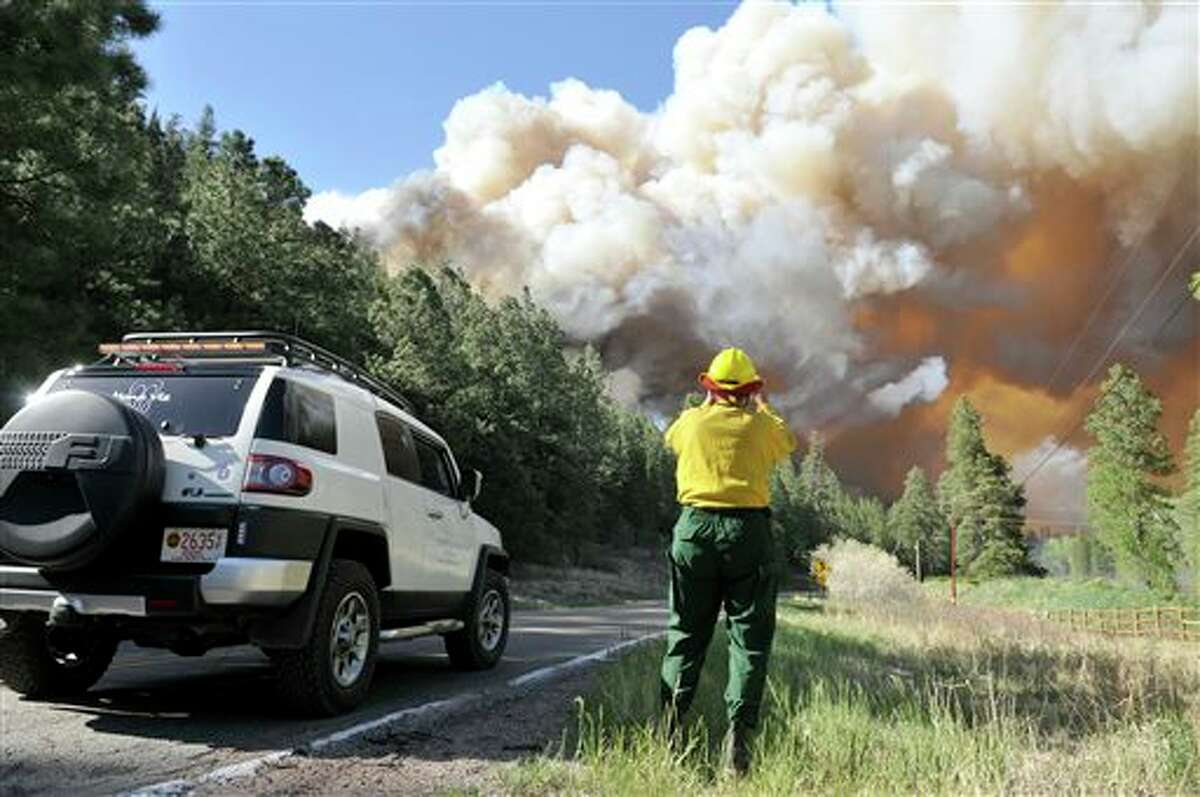 Bobb Barnes, with the Pecos Canyon Fire Department, blocks traffic as he watches a 100 acre fire burning out of control about 10 miles north of Pecos, N.M. on Thursday, May 30, 2013. A fast-moving blaze in New Mexico's Santa Fe National Forest prompted evacuations of residences and campgrounds, threatened upscale cabins and vacation homes, and closed a highway. Officials asked residents in 150 homes, mostly used for the summer , to evacuate as crews battled the 1,000-acre blaze near the communities of Pecos and Tres Lagunas, about 25 miles west of Santa Fe. (AP Photo/The Albuquerque Journal, Eddie Moore)