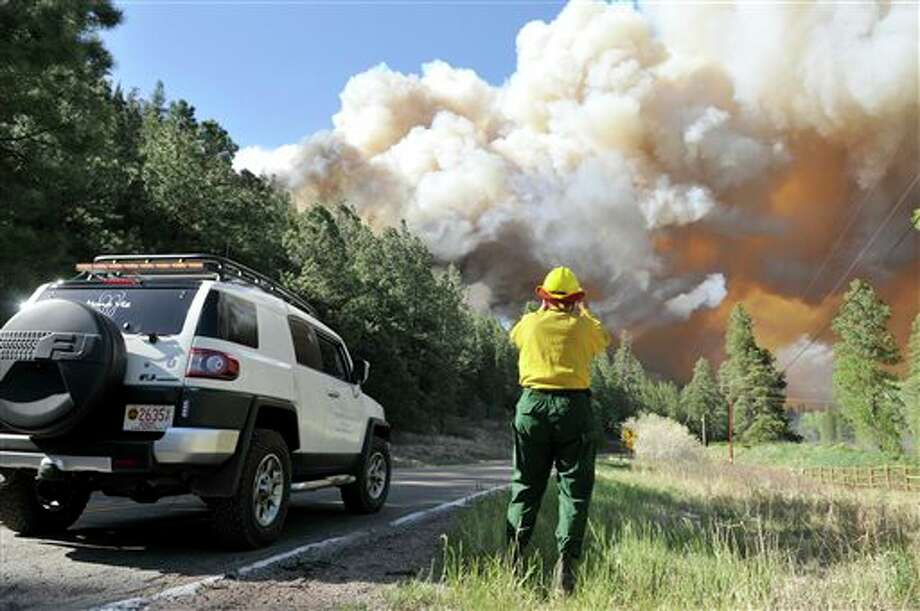 Bobb Barnes, with the Pecos Canyon Fire Department, blocks traffic as he watches a 100 acre fire burning out of control about 10 miles north of Pecos, N.M. on Thursday, May 30, 2013. A fast-moving blaze in New Mexico's Santa Fe National Forest prompted evacuations of residences and campgrounds, threatened upscale cabins and vacation homes, and closed a highway. Officials asked residents in 150 homes, mostly used for the summer , to evacuate as crews battled the 1,000-acre blaze near the communities of Pecos and Tres Lagunas, about 25 miles west of Santa Fe. (AP Photo/The Albuquerque Journal, Eddie Moore) Photo: Eddie Moore / The Albuquerque Journal