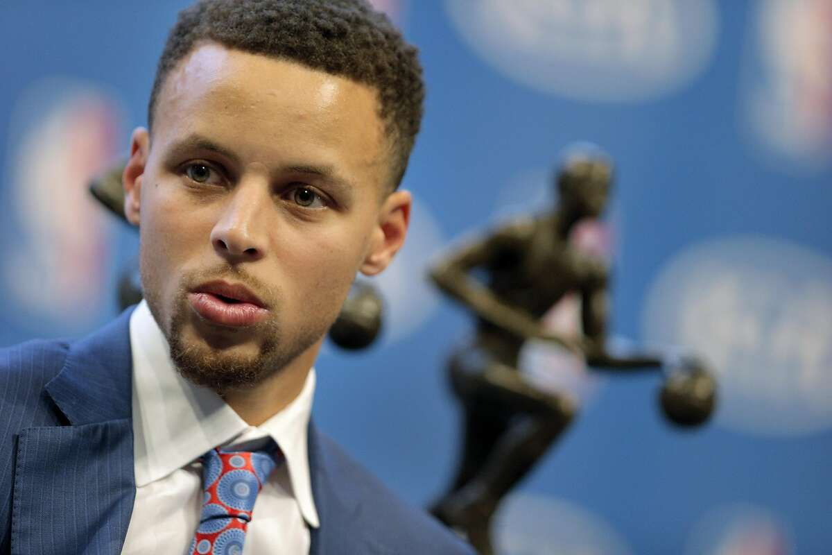 FILE - Stephen Curry waits on stage for a live interview with his two MVP trophies behind him following a ceremony where he was awarded the 2016 Kia NBA Most Valuable Player award during ceremony at Oracle Arena in Oakland, Calif., on Tuesday, May 10, 2016.