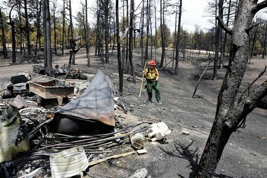 Firefighter Brandie Smith from Salida, Colo., walks past a burned out structure on the Black Forest wildfire north of Colorado Springs, Colo., on Monday, June 17, 2013. Over 470 homes burned in the wildfire that started last Tuesday. (AP Photo/Ed Andrieski) Photo: Ed Andrieski / AP