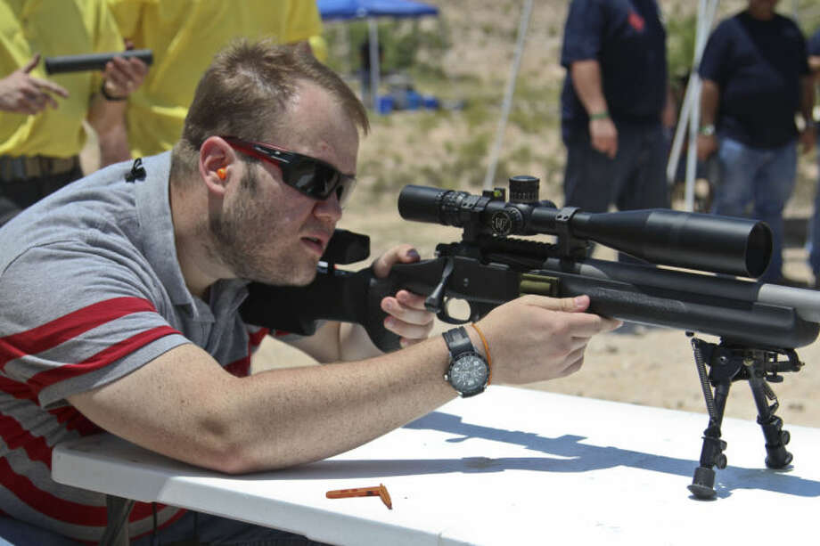 Reporter Tyler White looks through the scope of a bolt-action precision rifle during an open gun range event provided by S&K Arms Co. Sunday in Crane. James Durbin/Reporter-Telegram Photo: James Durbin
