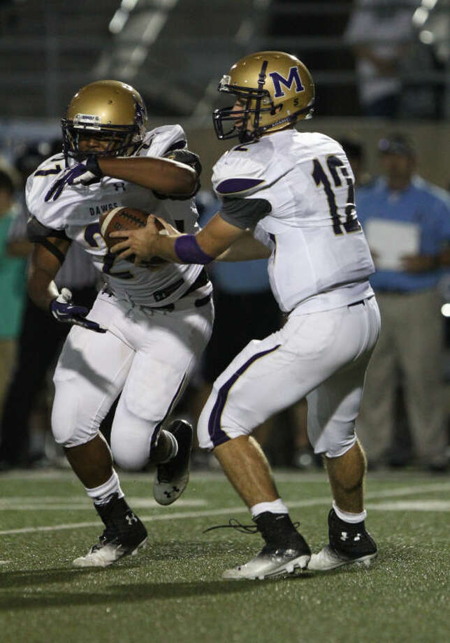 06 September 2013: Miidland Bulldogs quarterback Sam Grimes (12) hands the football off to running back Darius Reed (21) during the game between the LD Bell Blue Raiders and the Midland Bulldogs at Pennington Field in Bedford, Texas. Photo: Matt Pearce