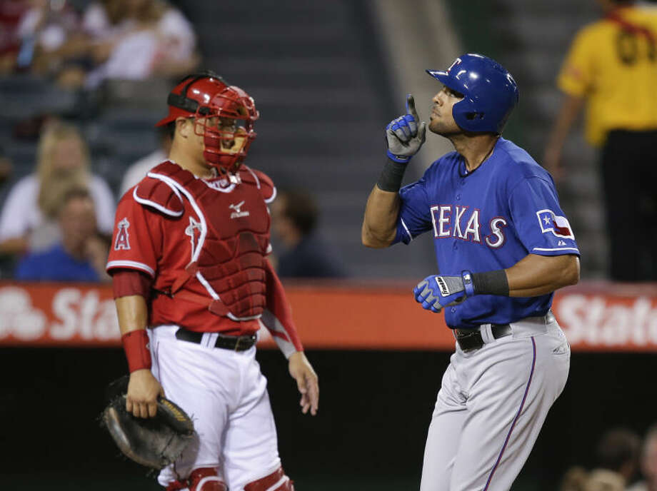 Texas Rangers' Alex Rios, right, celebrates his home run as he takes home plate past Los Angeles Angels catcher Hank Conger on Friday in Anaheim, Calif. (AP Photo/Jae C. Hong) Photo: Jae C. Hong