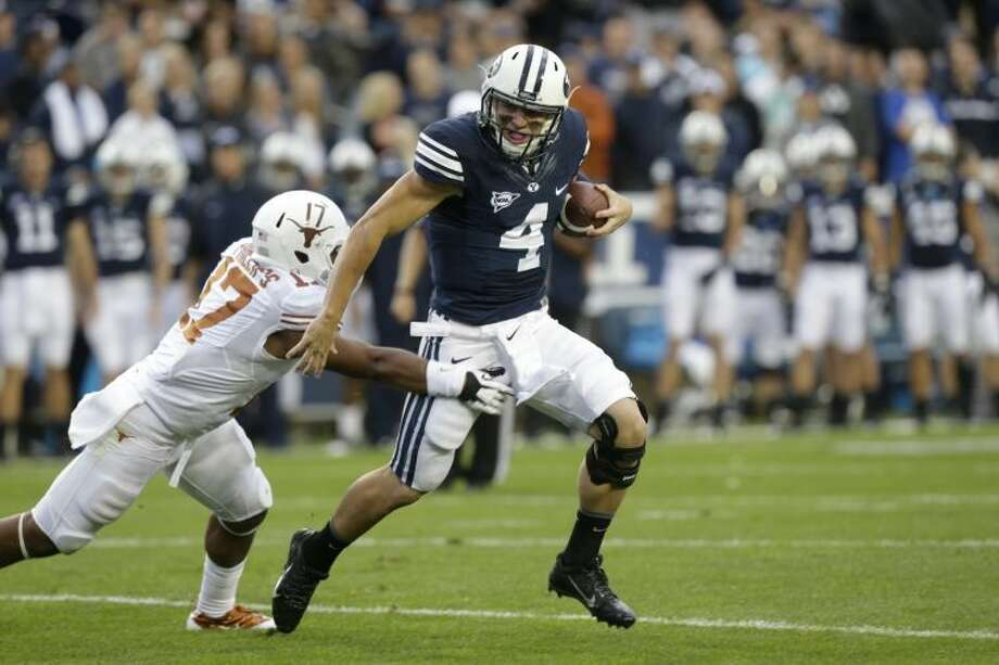 Texas safety Adrian Phillips (17) attempts to tackle Brigham Young quarterback Taysom Hill (4) in the first quarter during an NCAA college football game Saturday, Sept. 7, 2013, in Provo, Utah. (AP Photo/Rick Bowmer) Photo: Rick Bowmer