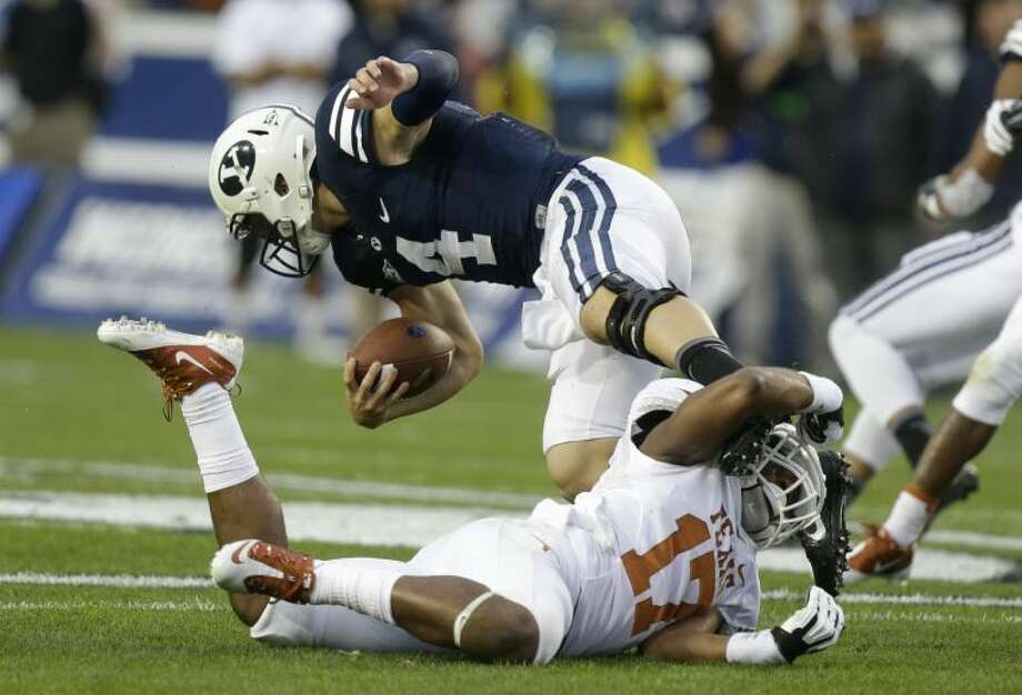 Texas safety Adrian Phillips (17) tackles Brigham Young quarterback Taysom Hill (4) in the first half of their game Saturday in Provo, Utah. Photo: Rick Bowmer