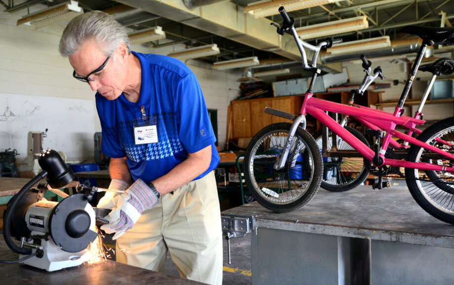Kent Crowell, a robotics and technology education teacher at San Jacinto Junior High, grinds a piece of metal for his custom tandem bike project (in background) Wednesday in the San Jacinto shop. James Durbin/Reporter-Telegram Photo: JAMES DURBIN