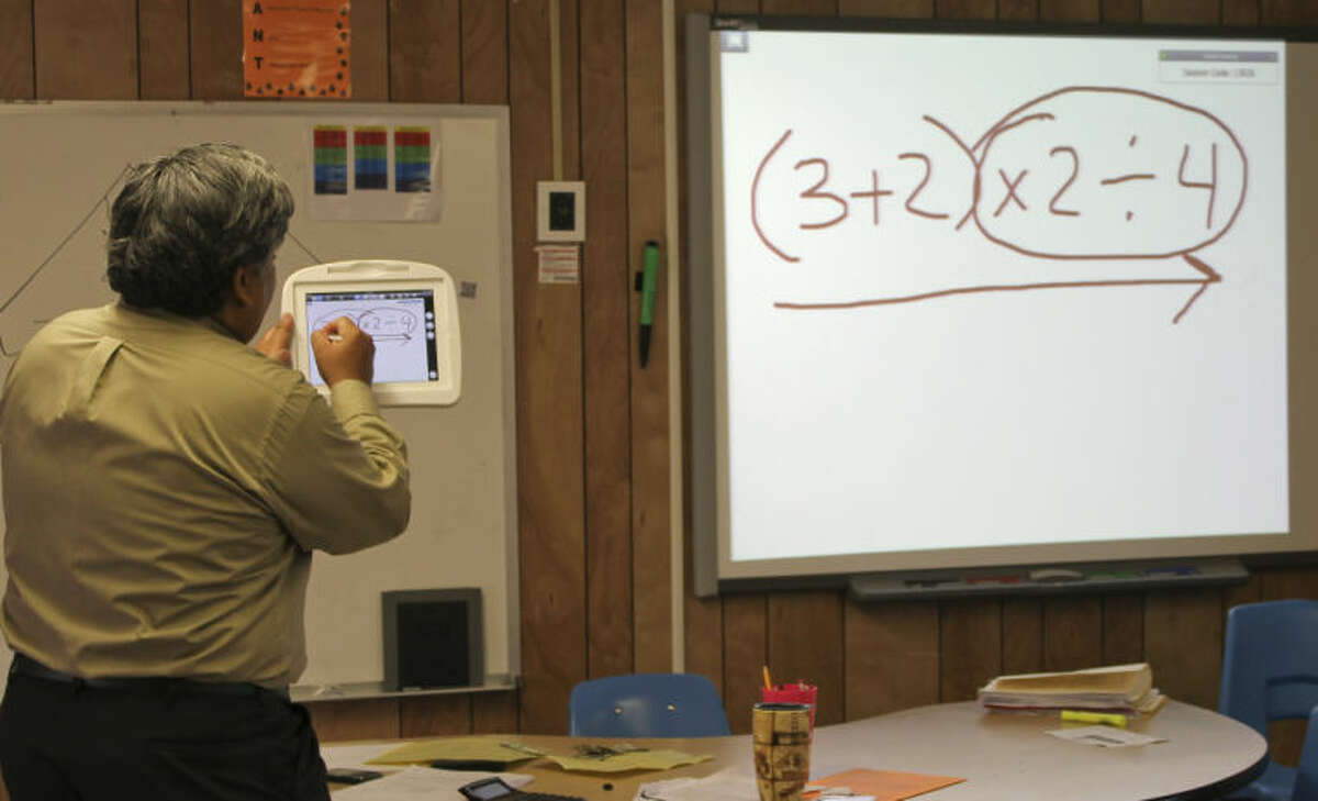 Pease Communication and Technology Academy teacher Francisco Torres teaches sixth grade students about order of operations by using his iPad to project math problems on the classroom's SMART board. Meredith Moriak/Reporter-Telegram