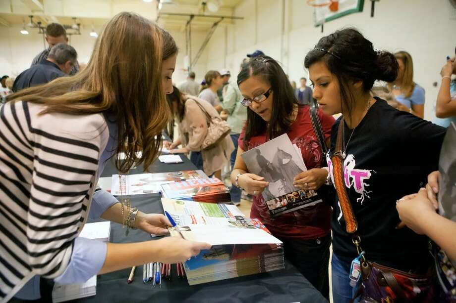 Texas Tech University Admissions Counselor Jessica Cravens goes over enrollment information with Elizabeth Estrada, left, and her daughter Sarah, 17, Wednesday College Forum at Midland College. College Forum is a joint project between Midland College and Midland Independent School District which gives students an opportunity to learn about the opportunities that await them when they complete high school. Cindeka Nealy/Reporter-Telegram Photo: Cindeka Nealy