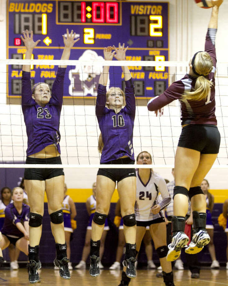 Lee's Ashley Carter (7) tries to hit past Midland's Jenna Gillean (23) and Channing Burleson (10) Tuesday at Midland High. Midland beat Lee in five sets. James Durbin/Reporter-Telegram Photo: JAMES DURBIN
