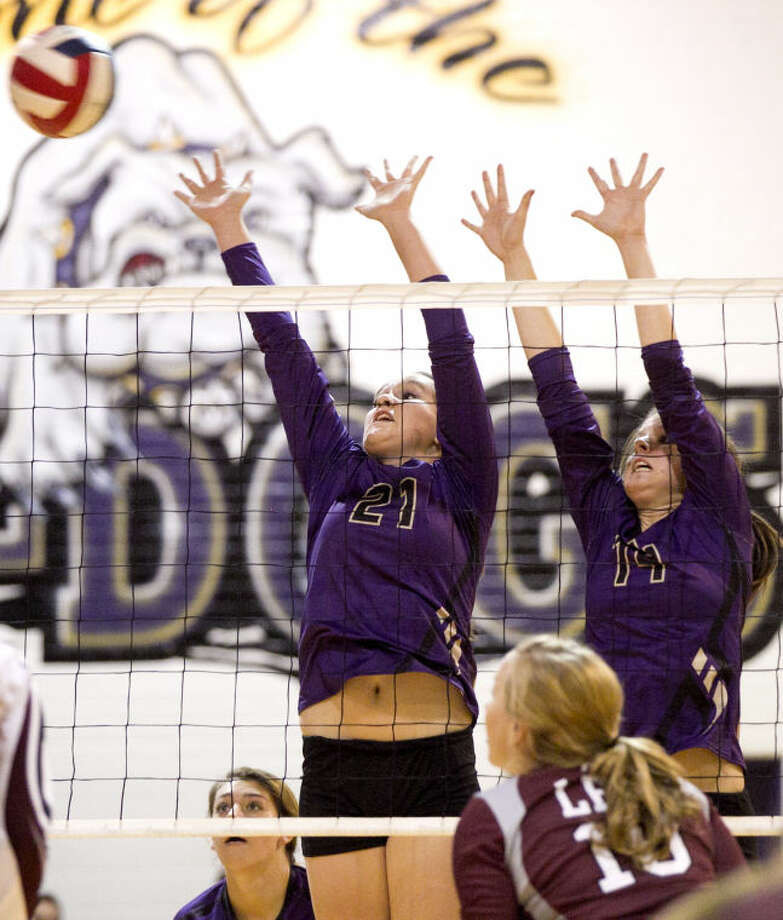 Midland's Shelby Neatherlin (21) and Kaydee Strickland (14) try to block a hit from the Lee offense Tuesday at Midland High. Midland beat Lee in five sets. James Durbin/Reporter-Telegram Photo: JAMES DURBIN