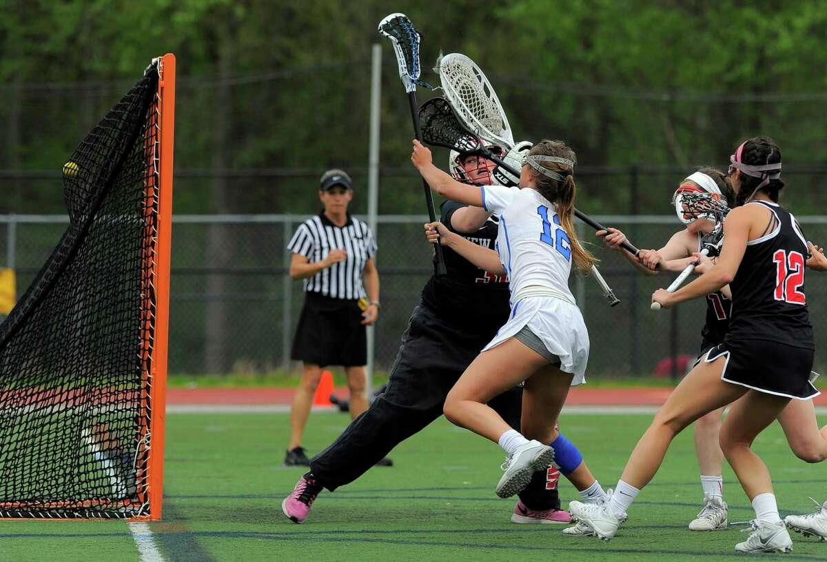 Darien Susannah Ropp (12) fires a shot past New Canaan goalie Caroline O'Dea in a FCIAC girls lacrosse game at Darien High School on May 10, 2016. Darien defeated New Canaan 20-10.