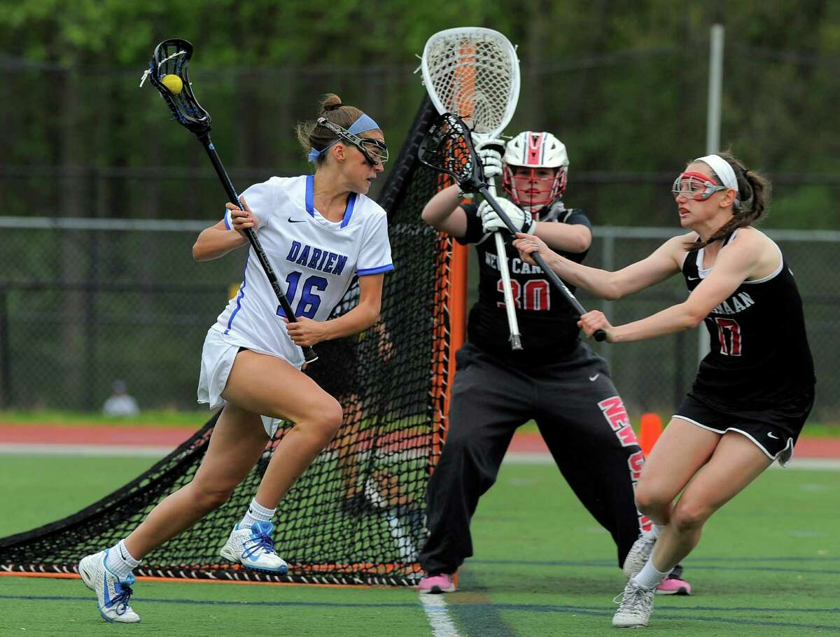 Darien Anna Stein looks for an opening under pressure from New Canaan Julia Ozimek in a FCIAC girls lacrosse game at Darien High School on May 10, 2016. Darien defeated New Canaan 20-10.