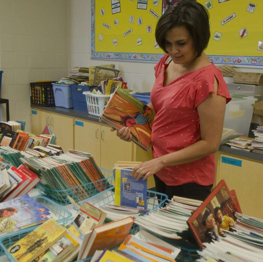 Diana Arroyos, new 5th grade reading teacher at Jane Long Elementary, picks out books for her classroom Monday during a book giveaway sponsored by Midland Reading Council and Scholastic. Tim Fischer/Reporter-Telegram Photo: Tim Fischer