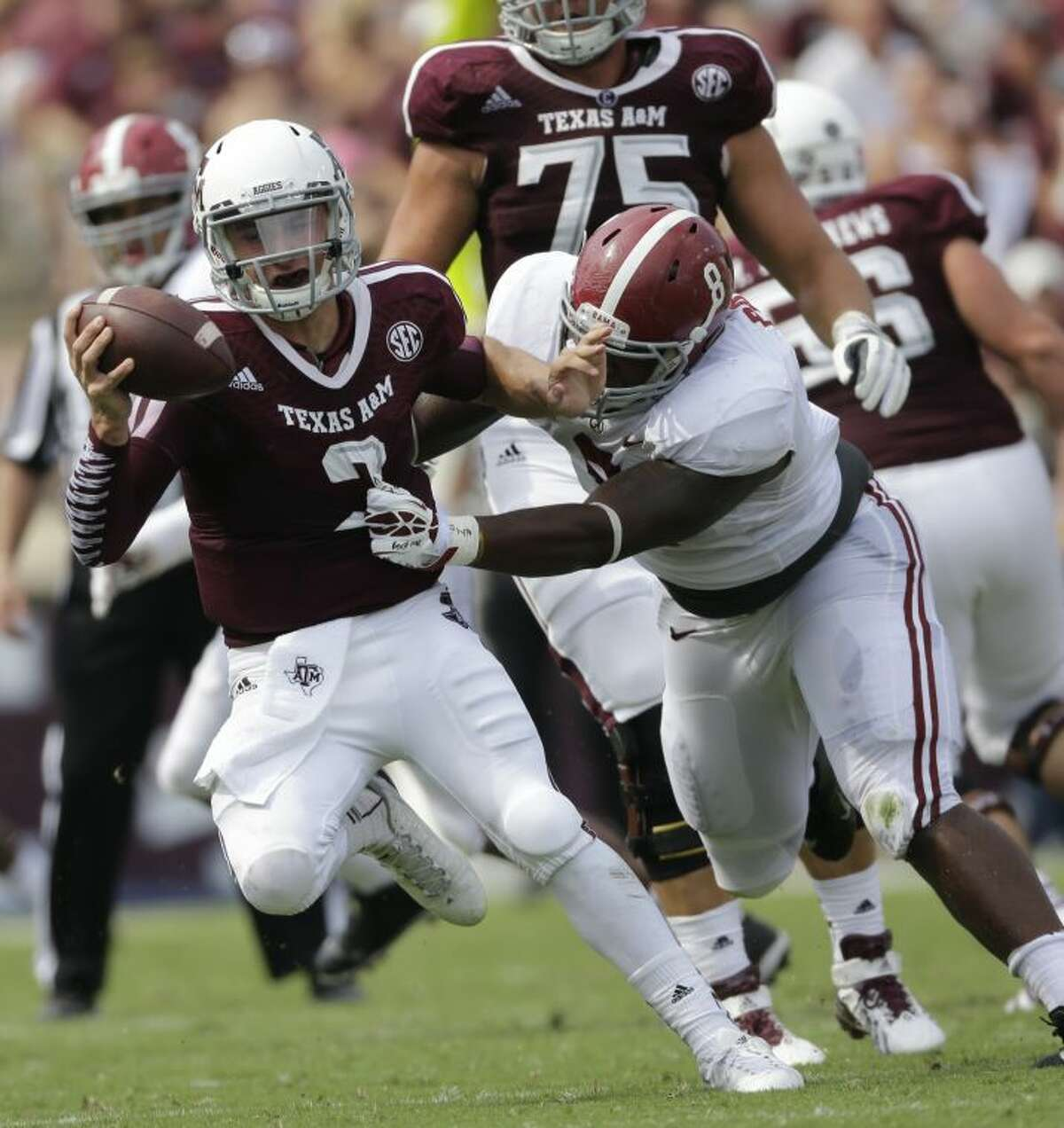 Texas A&M quarterback Johnny Manziel (2) escapes from Alabama defensive lineman Jeoffrey Pagan (8) during the second quarter of an NCAA college football game Saturday, Sept. 14, 2013 in College Station, Texas. (AP Photo/David J. Phillip)