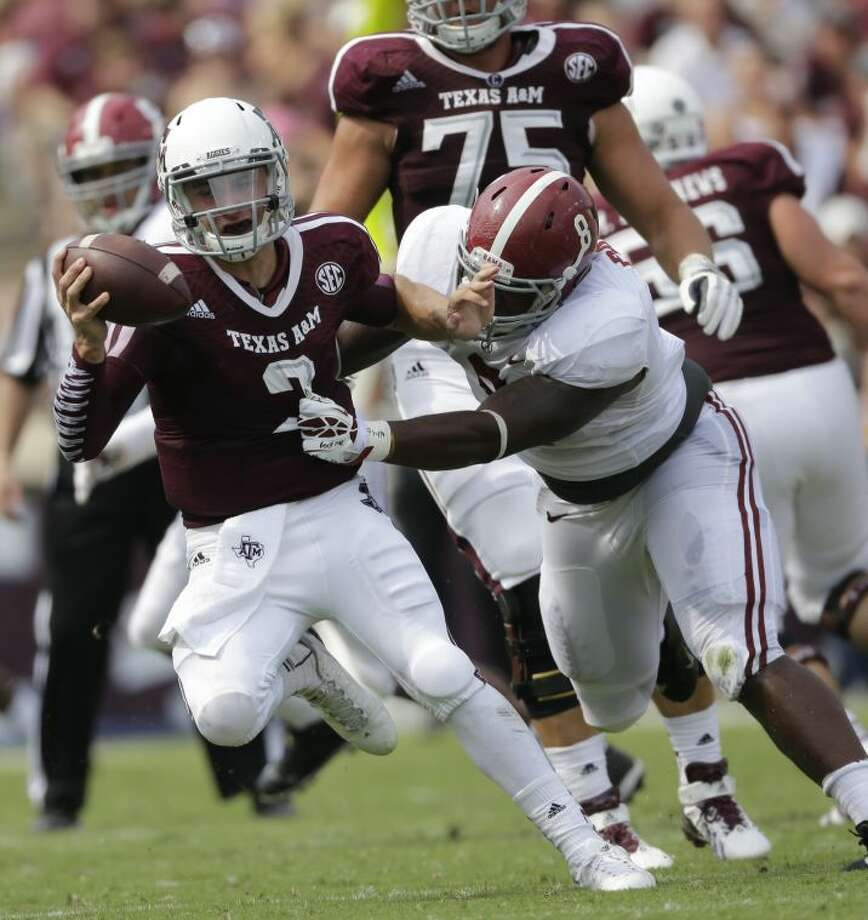 Texas A&M quarterback Johnny Manziel (2) escapes from Alabama defensive lineman Jeoffrey Pagan (8) during the second quarter of an NCAA college football game Saturday, Sept. 14, 2013 in College Station, Texas. (AP Photo/David J. Phillip) Photo: David J. Phillip