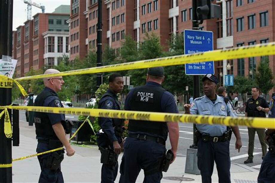 Police work the scene on M Street, SE in Washington near the Washington Navy Yard on Monday, Sept. 16, 2013. The U.S. Navy says one person is injured after a shooting at a Navy building in Washington. Police and emergency crews gathered Monday morning outside the Naval Sea Systems Command Headquarters building, where the shooting was reported. (AP Photo/Jacquelyn Martin) Photo: Jacquelyn Martin / AP2013