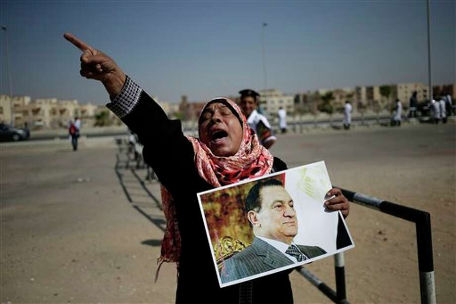 An Egyptian woman carrying a photo of ousted president Hosni Mubarak chants slogans against ousted President Mohammed Morsi and the Muslim Brotherhood as she expresses her support for Mubarak at a court in Cairo, Egypt, Saturday, Sept. 14, 2013. The ousted long-time autocrat went back in court as his trial resumed on charges related to the killings of some 900 protesters during the 2011 uprising that led to his ouster. (AP Photo/Hassan Ammar) Photo: Hassan Ammar / AP