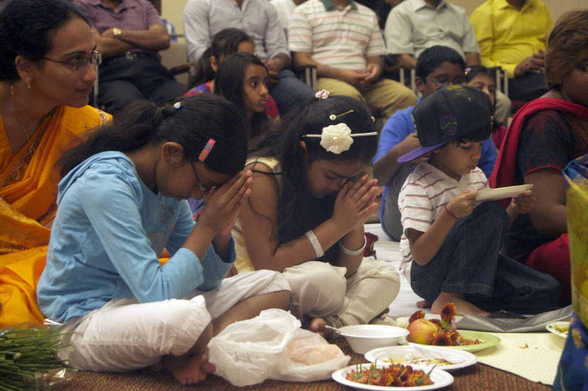 Children pray during a puja ceremony for Ganesha at the Hindu Association of West Texas temple.