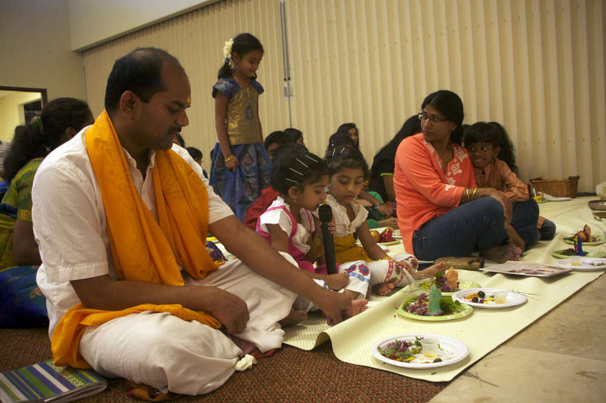 Pavani and Hamsini Vignesh (center) sing a prayer song during a puja ceremony at the Hindu Association of West Texas Temple.