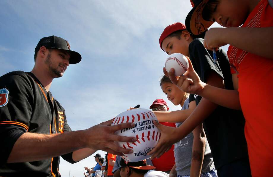 Pitcher Tyler Beede, 63 signs a giant base for Jamison and Kylie Husbands of San Clemente, Ca. as the San Francisco Giants prepare to play the Los Angeles Angels at Scottsdale Stadium on Wed. March 2,  2016, in Scottsdale, Arizona. Photo: Michael Macor / The Chronicle