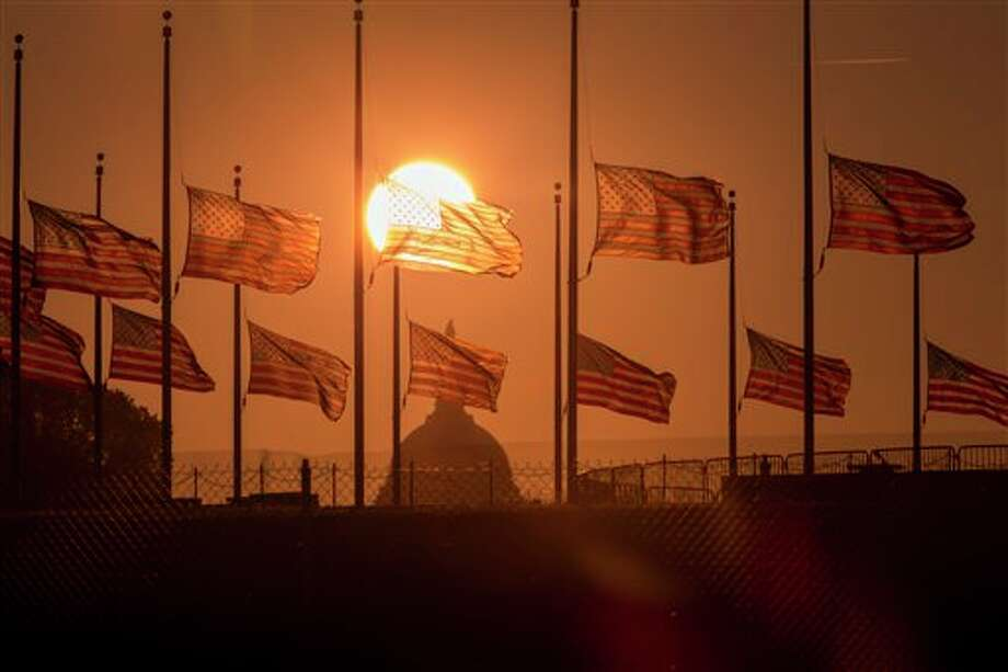 The American flags surrounding the Washington Monument fly at half-staff as ordered by President Barack Obama following the deadly shooting Monday at the Washington Navy Yard, Tuesday morning, Sept. 17, 2013, in Washington. (AP Photo/J. Scott Applewhite) Photo: J. Scott Applewhite / AP