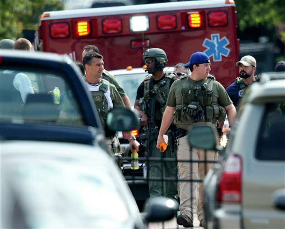 Police officers responding to shooting at the Washington Navy Yard, Monday, Sept. 16, 2013, leave the facility. At least one gunman launched an attack inside the Washington Navy Yard, spraying gunfire on office workers in the cafeteria and in the hallways at the heavily secured military installation in the heart of the nation's capital, authorities said (AP Photo/Manuel Balce Ceneta) Photo: Manuel Balce Ceneta / AP