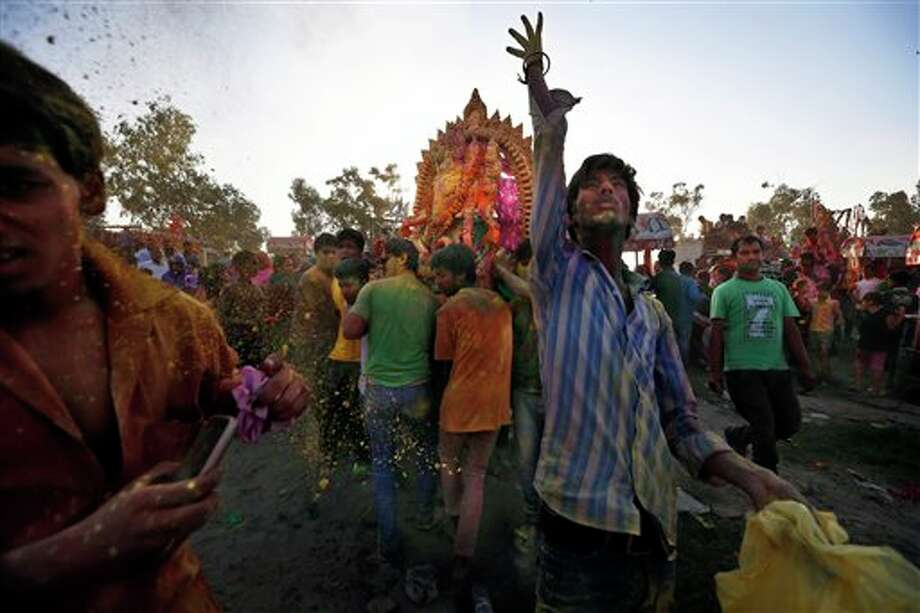A devotee throws colored powder as others carry a statue of elephant-headed Hindu God Ganesha to immerse into the River Yamuna in New Delhi, India, Wednesday, Sept. 18, 2013. The immersion marks the end of the ten-day long Ganesh Chaturthi festival that celebrates the birth of the Hindu God of wisdom, prosperity and good fortune. (AP Photo/Saurabh Das) Photo: Saurabh Das / AP