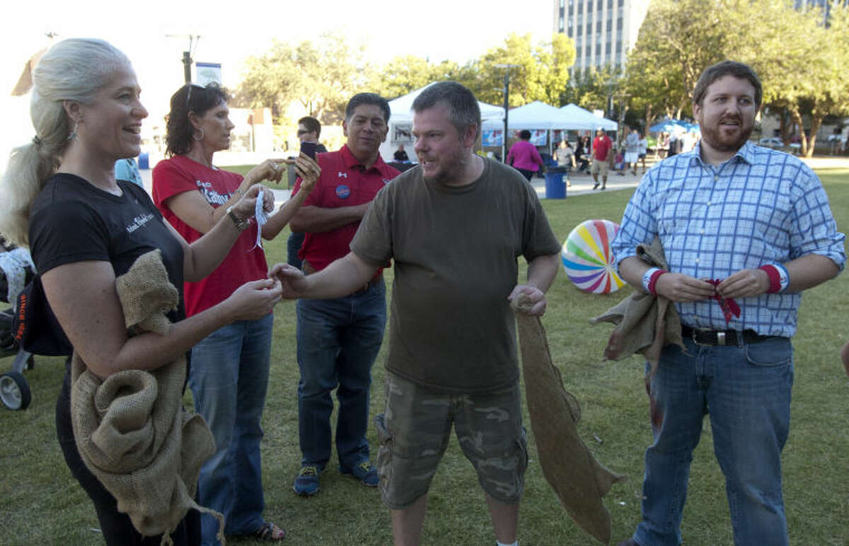 Mayoral candidate Kathy White receives her ribbon after finishing second in a sack race against fellow candidates Dan Anderson, Jerry Morales and Keith McLelland during the Fiesta on the Plaza on Saturday at Centennial Plaza. James Durbin/Reporter-Telegram