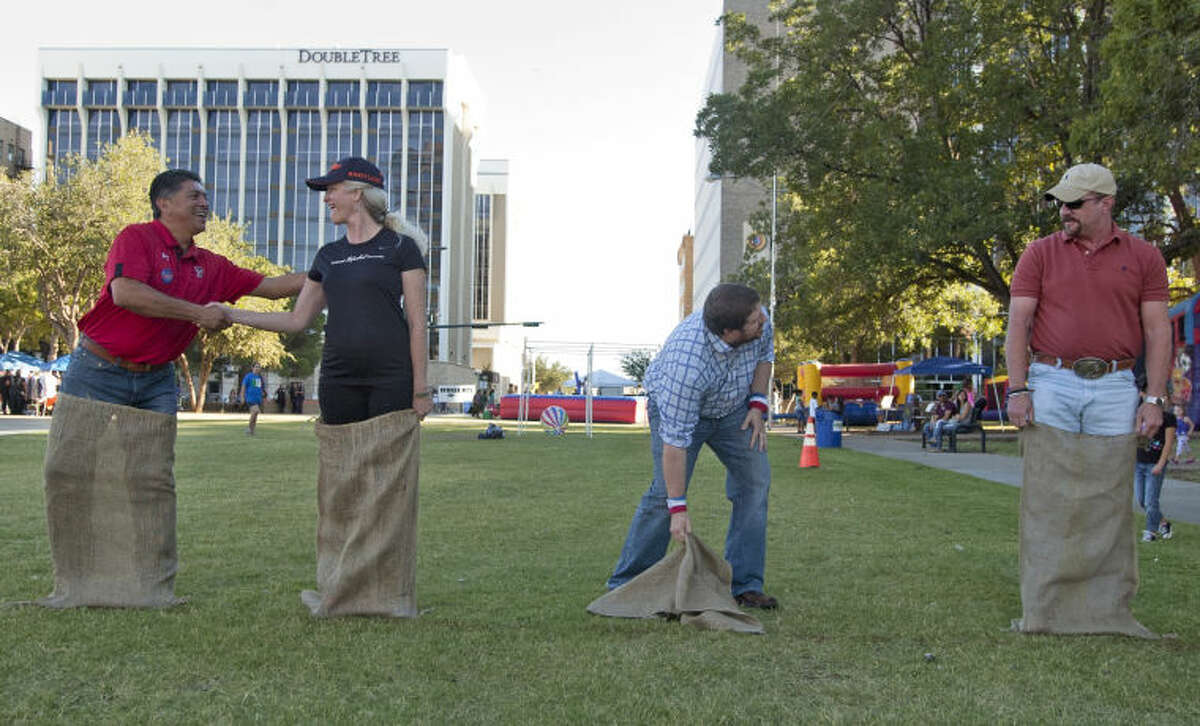 From left, mayoral candidates Jerry Morales, Kathy White, Dan Anderson, and Keith McLelland prepare for a sack race during the Fiesta on the Plaza on Saturday at Centennial Plaza. Morales finished first, Anderson finished second, White finished third and McLelland finished fourth. James Durbin/Reporter-Telegram