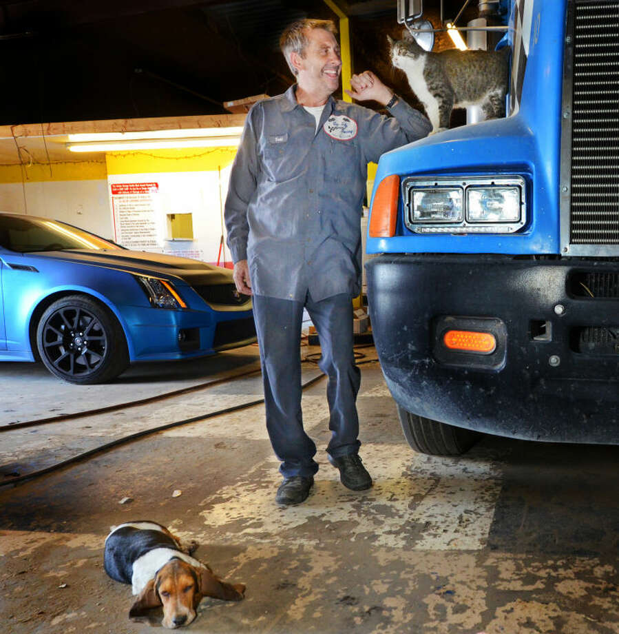 "Todd Turner, owner of Big Sky Towing, stands with his 16-year-old cat named ""Nibbles"" and a hound puppy named ""Fred"" in his shop with a Kenworth T600 towing rig and his supercharged Cadillac CTS-V coupe on Wednesday. James Durbin/Reporter-Telegram Photo: JAMES DURBIN"