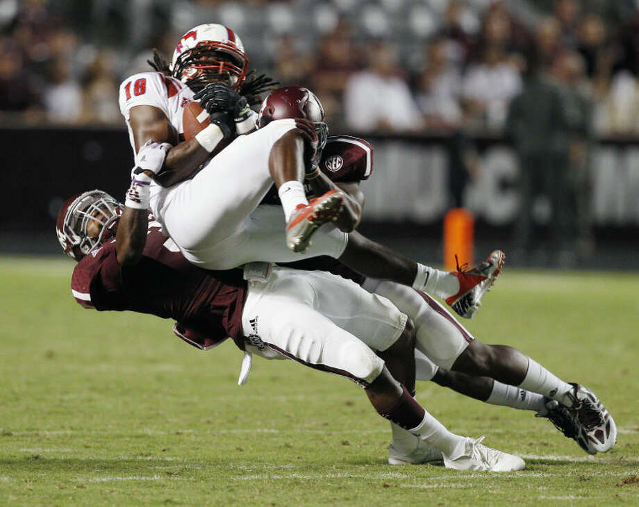 Texas A&M linebacker Tommy Sanders (3) tackles SMU wide receiver J'Marcus Rhodes (18) Saturday in College Station. Texas A&M won 42-13. (AP Photo/Bob Levey) Photo: Bob Levey
