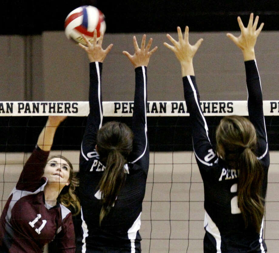 Midland Lee Bentleigh Dunavan spikes the ball against Permian defenders in the third set of the match Tuesday at the Permian Fieldhouse. Photo: Edyta Blaszczyk | Odessa America