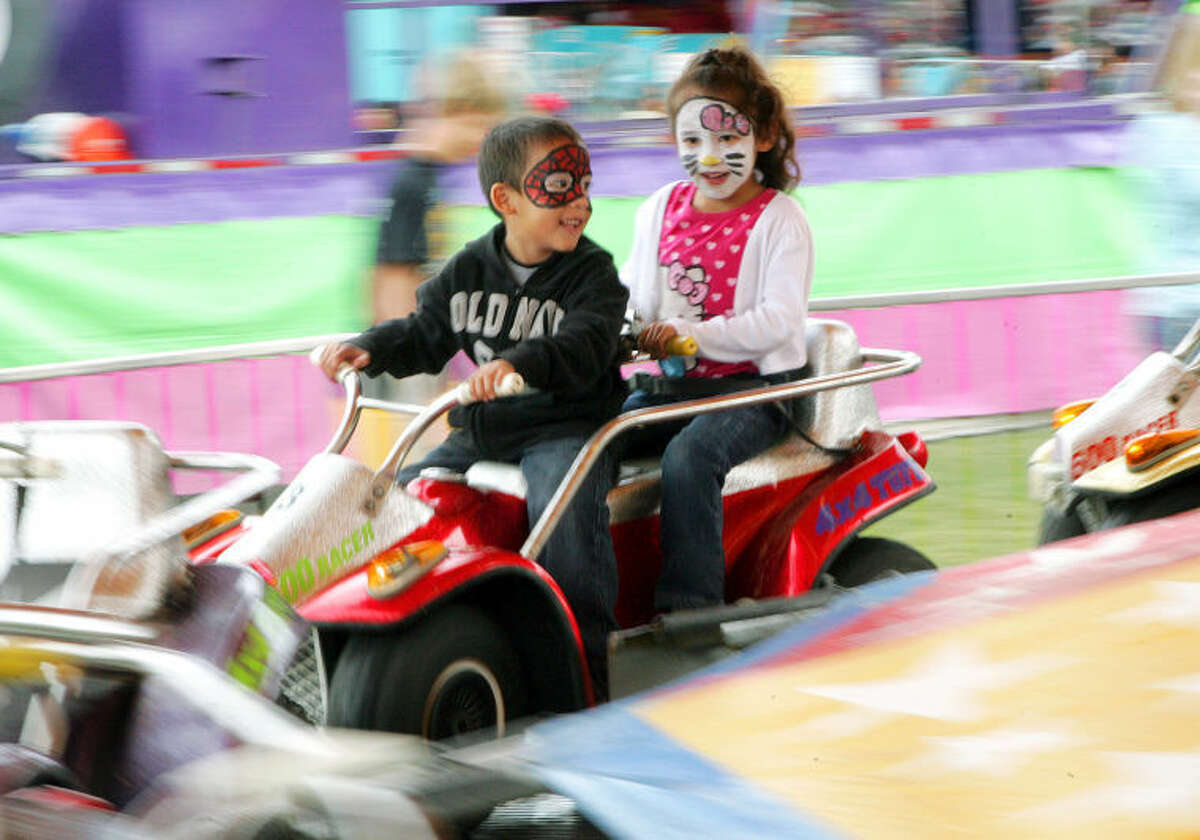 Aiden and Nadia Trujilo, 5, take a ride on a carnival attraction at the St. Ann's fair Saturday. James Durbin/Reporter-Telegram