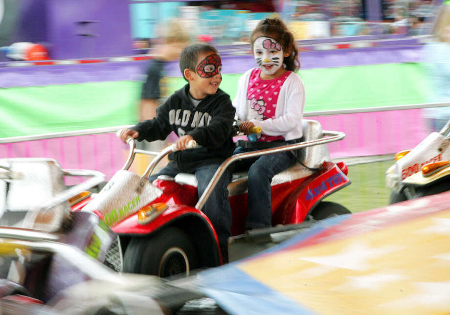 Aiden and Nadia Trujilo, 5, take a ride on a carnival attraction at the St. Ann's fair Saturday. James Durbin/Reporter-Telegram Photo: JAMES DURBIN